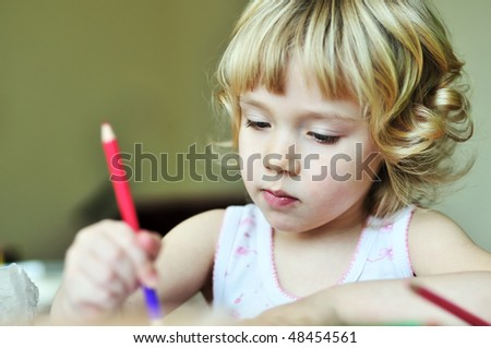 serious little girl drawing in soft focus
