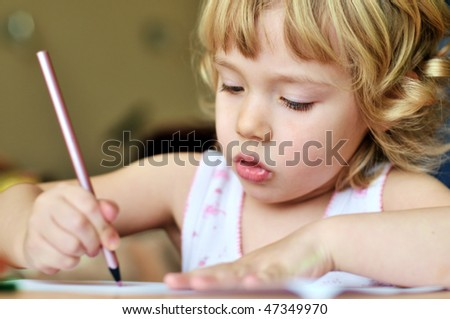 serious little girl drawing in soft selective focus