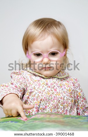 Serious little girl in glasses reading book