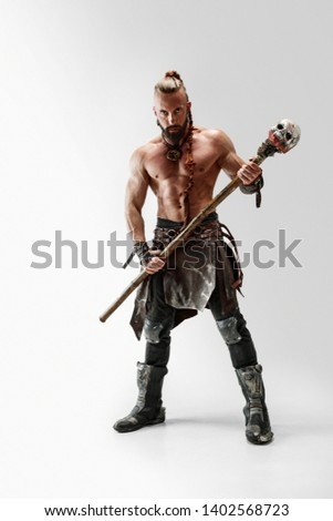Serious long hair and muscular male model in leather viking's costume with the big mace cosplaying isolated on white studio background. Full-length portrait. Fantasy warrior, antique battle concept.