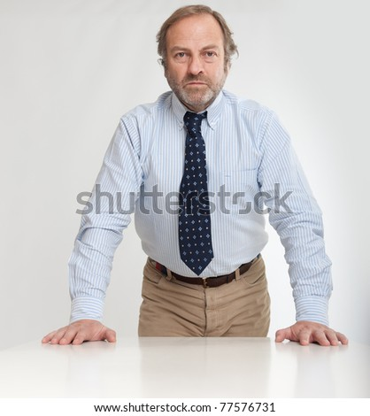 Serious looking business man leaning on a table