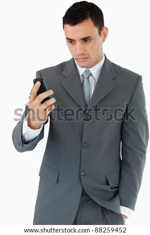 Serious looking businessman looking at his cellphone against a white background