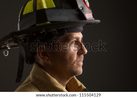 Serious looking confident firefighter Headshot Profile View Portrait on Dark Background