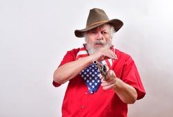 Serious looking cowboy aiming his revolver at the camera. Angry man looking serious, wearing a patriotic bandana and point his gun right at the camera.