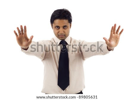 Serious looking Indian businessman with his hands raised in signal to stop isolated over white background