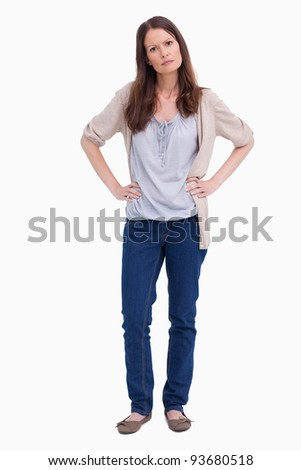 Serious looking woman with her hands on her hips against a white background
