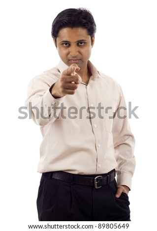 Serious looking young indian business man pointing finger at you isolated over white background