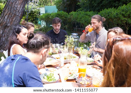 Serious male and female friends having dinner outdoors. Young women and men eating salads and drinking juice in garden. Outdoor party concept