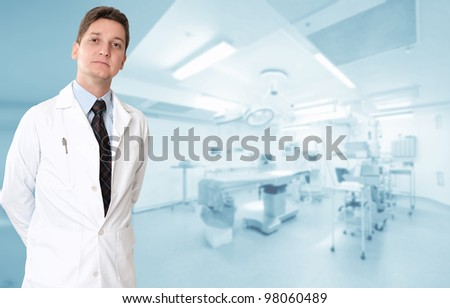 Serious male doctor with an operating room at the background