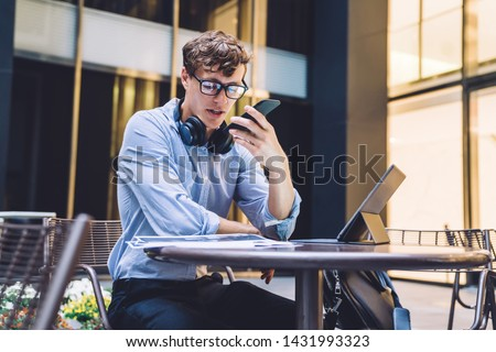 Serious male entrepreneur recording voice message during online communication with personal secretary solving problems while checking mistakes on financial report, concept of business people