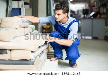 serious male in uniform is choosing cement in the building store room