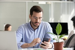 Serious male office manager work in coworking space using smartphone analyzing online market trends, focused man worker reading financial news or browsing internet on phone. Technology concept