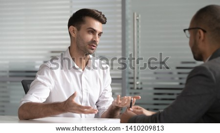 Serious male professional salesman consult customer at business meeting, applicant talk with hr at job interview, bank investment advisor lawyer give legal advice explain insurance loan deal benefits
