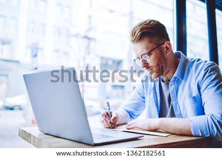 Serious male student writing school test in knowledge textbook during e learning in campus cafeteria, young hipster guy in eyewear for vision correction studying indoors doing homework in notepad