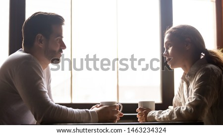 Serious man and woman sitting at cafe table drinking coffee talking and chatting, millennial colleagues or friends spend lunch break in coffeehouse speaking and sharing news enjoying hot beverage