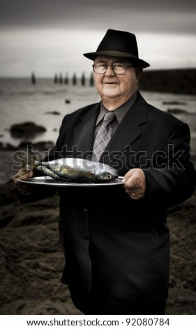 Serious Man At Dark Beachfront Holding A Plate Of Fish With A Questioning Expression In A Fisheries Over Consumption Of Natural Resources
