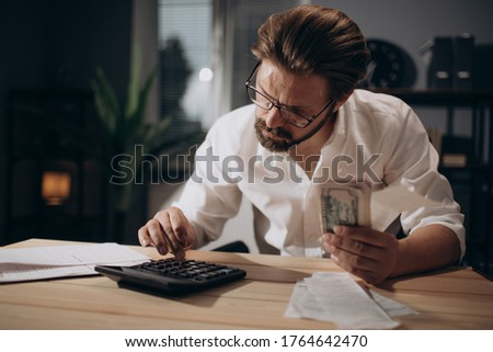Serious man checking bills and counting money at office Foto stock ©