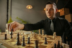 Serious man chess player sitting at home and playing chess alone.
