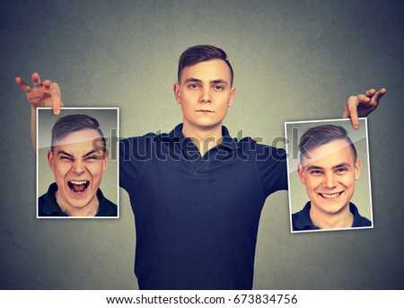 Serious man holding two different face emotion masks of himself