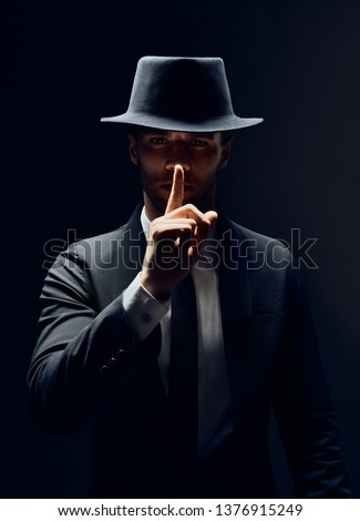 Serious man in black suit and hat keeps finger on lips, making hush gesture and keep conspiracy isolated on dark background. Shh, silence concept