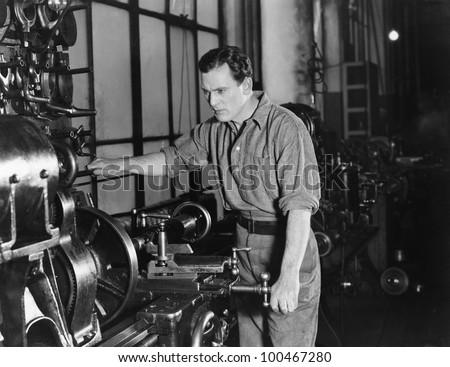 Serious man using large machine