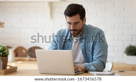 Serious man wearing glasses working on laptop online, sitting at table in kitchen, looking at computer screen, focused male using internet banking service, writing email, searching information