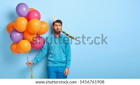 Serious man wears cone birthday hat, blows in party whistle, holds colorful air balloons, dressed in neat blue clothes, stands indoor, celebrates anniversary. Blank copy space for your information #1456761908