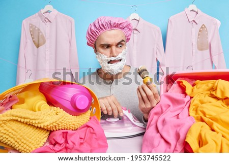 Serious man with foam gel on face gazes attentively at shaving brush busy doing hygiene procedures at home ironing clothes poses near laundry baskets full of washed linen chemical detergents ストックフォト ©
