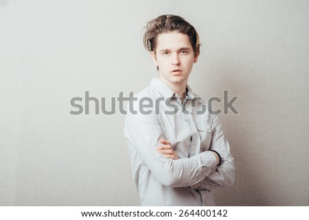 serious man with hands folded on grey background