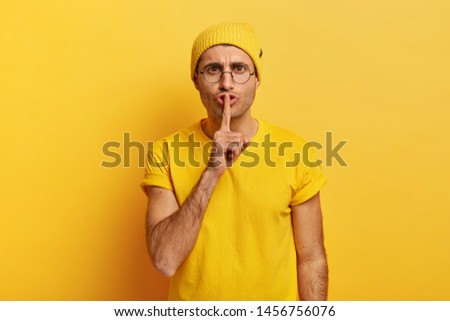 Serious man with mysterious look, keeps index finger over lips, looks straightly at camera, demands complete silence, makes hush sign, wears big roud glasses, yellow clothes. Secrecy concept