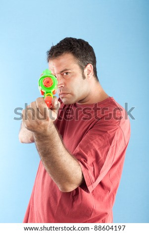 Serious man with toy gun pointing at camera