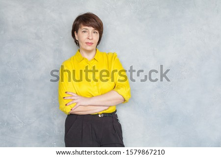 Serious mature business woman in yellow shirt portrait
