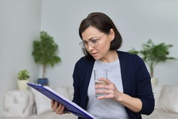 Serious mature business woman with glasseswith a glass of water reading paper files