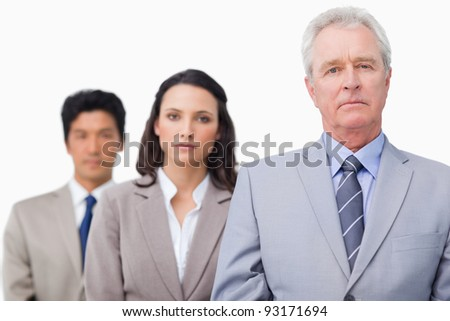 Serious mature businessman with his team against a white background