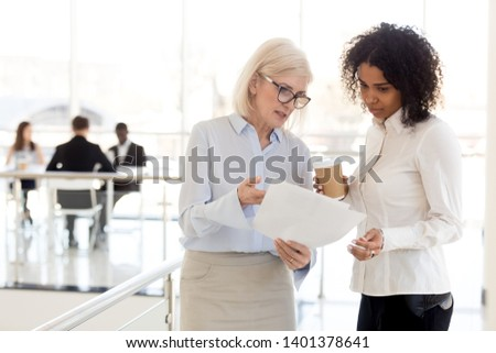 Serious mature businesswoman show document to African American female colleague during break, middle-aged boss explaining task, point at mistake to subordinate, diverse employees discuss paperwork