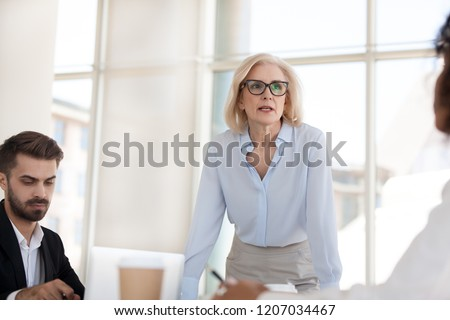 Serious mature businesswoman stand talk with employees at office meeting, middle aged female boss discuss project or strategy with workers at office briefing, confident woman negotiate with colleagues