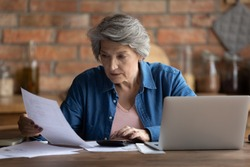 Serious mature Caucasian 60s woman sit at table calculate household finances paying bills on laptop online. Focused senior grey-haired grandmother manage family home budget, read paper bank notice