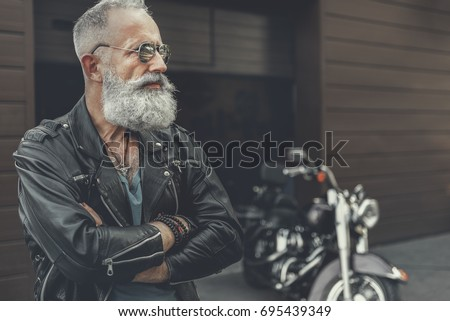 Serious mature male person locating near building
