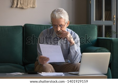 Serious mature man wearing glasses sitting on couch in living room manage budget received invoice analyzes month expenses feels concerned about public utility debt, check read loan documents concept