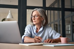 Serious mature older adult woman watching training webinar on laptop working from home or in office. 60s middle aged businesswoman taking notes while using computer technology sitting at table.