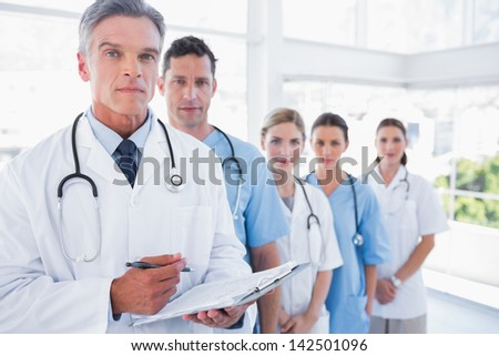 Serious medical team in row in a bright hospital