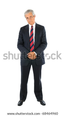 Serious middle aged businessman in a suit and tie standing with hands clasped in front peering over the top of his glasses. Full length over a white background.