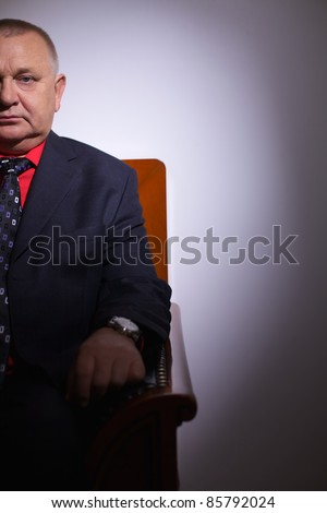 Serious middle aged businessman in suit sitting on leather sofa in office indoor