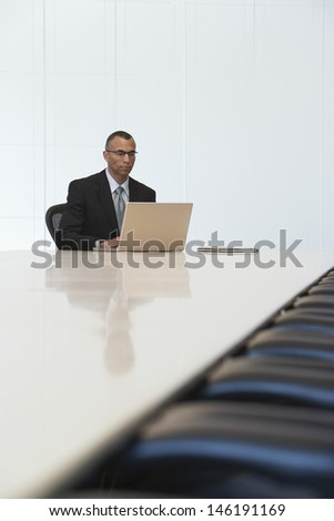 Serious middle aged businessman using laptop in board room - stock photo