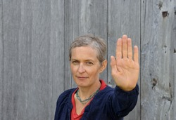 Serious middle-aged Caucasian country woman with short hair makes the hand palm stop sign with her left hand (stop gesture, palm facing outwards), in front of an old barn wood background.