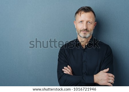 Serious middle-aged man with folded arms and a deadpan expression posing in front of a grey background with copy space #1016721946