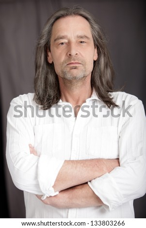 Serious middle-aged man with shoulder length hair standing with his arms folded looking at the camera, upper body studio portrait