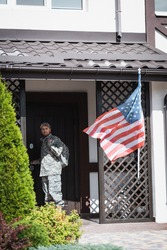 Serious military man standing near house door and looking away near bushes and american flag