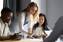 Serious millennial blonde female team leader analyzing financial or marketing paper document, reporting research results to focused multiracial young and older business partners colleagues at office.