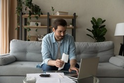 Serious millennial male in glasses focused on paying utility bills taxes rental charges online using laptop. Young man working from home office sit on couch hold paper invoice check information online
